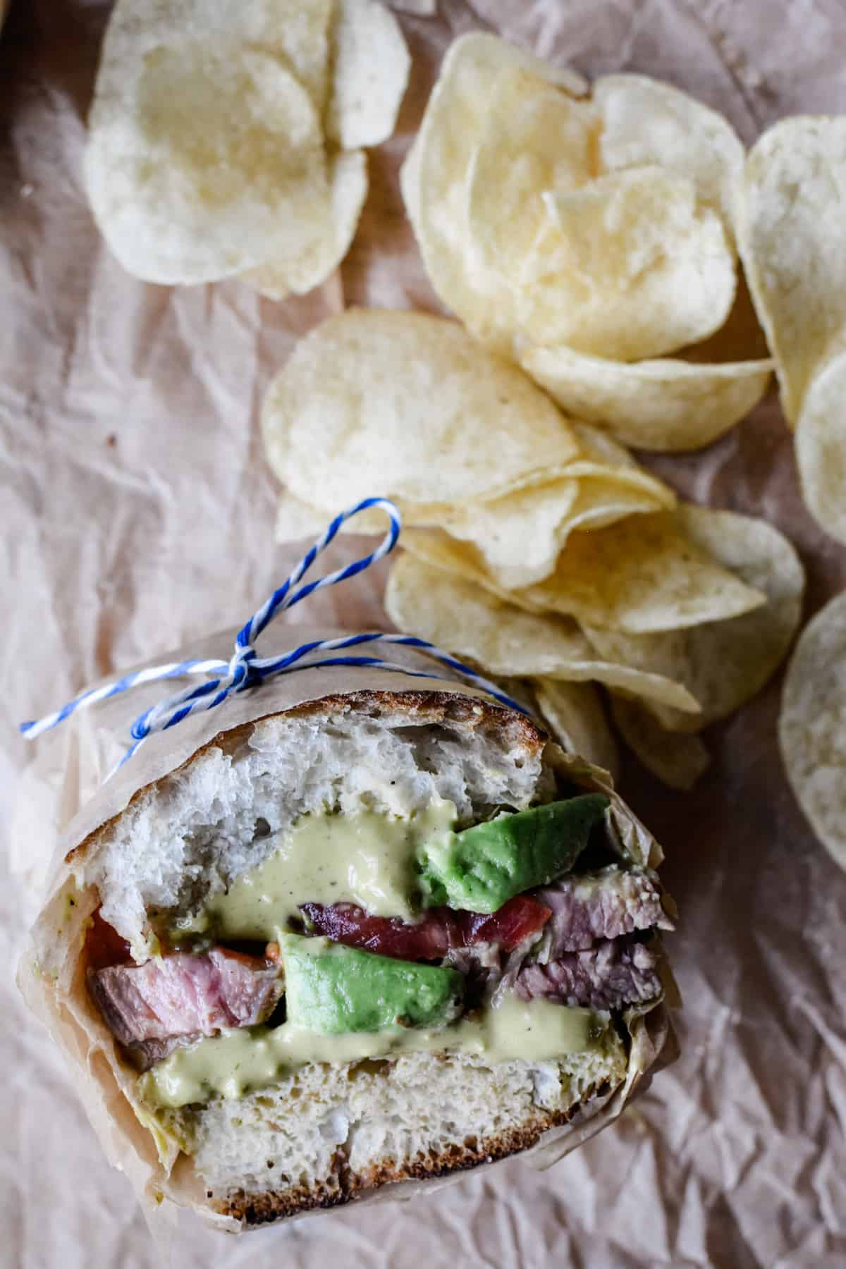 Half of a Carne Asada Torta sitting on a piece of brown parchment paper with potato chips on the side. The sandwich is wrapped in paper with a blue and white string around it.