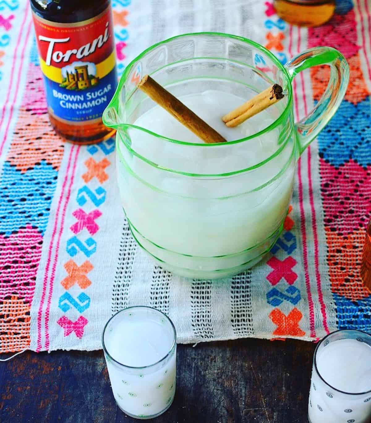 A pitcher of horchata sitting on a table with two cinnamon sticks in it.