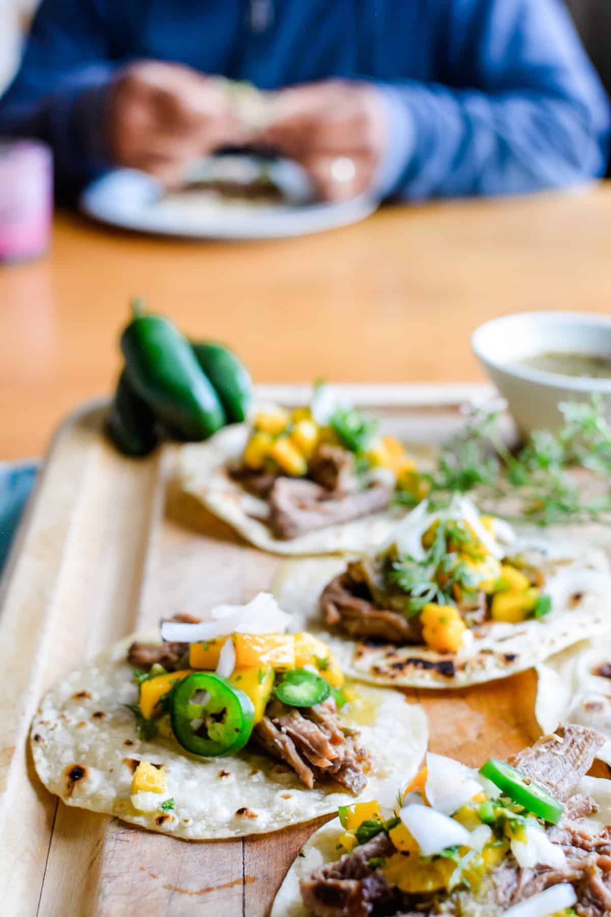 Several beef tacos sitting on a wooden cutting board with a man eating tacos sitting in the background out of focus.