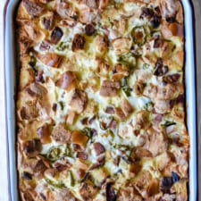 An overhead shot of a ham and cheese breakfast casserole in a white baking dish sitting on a white table cloth.
