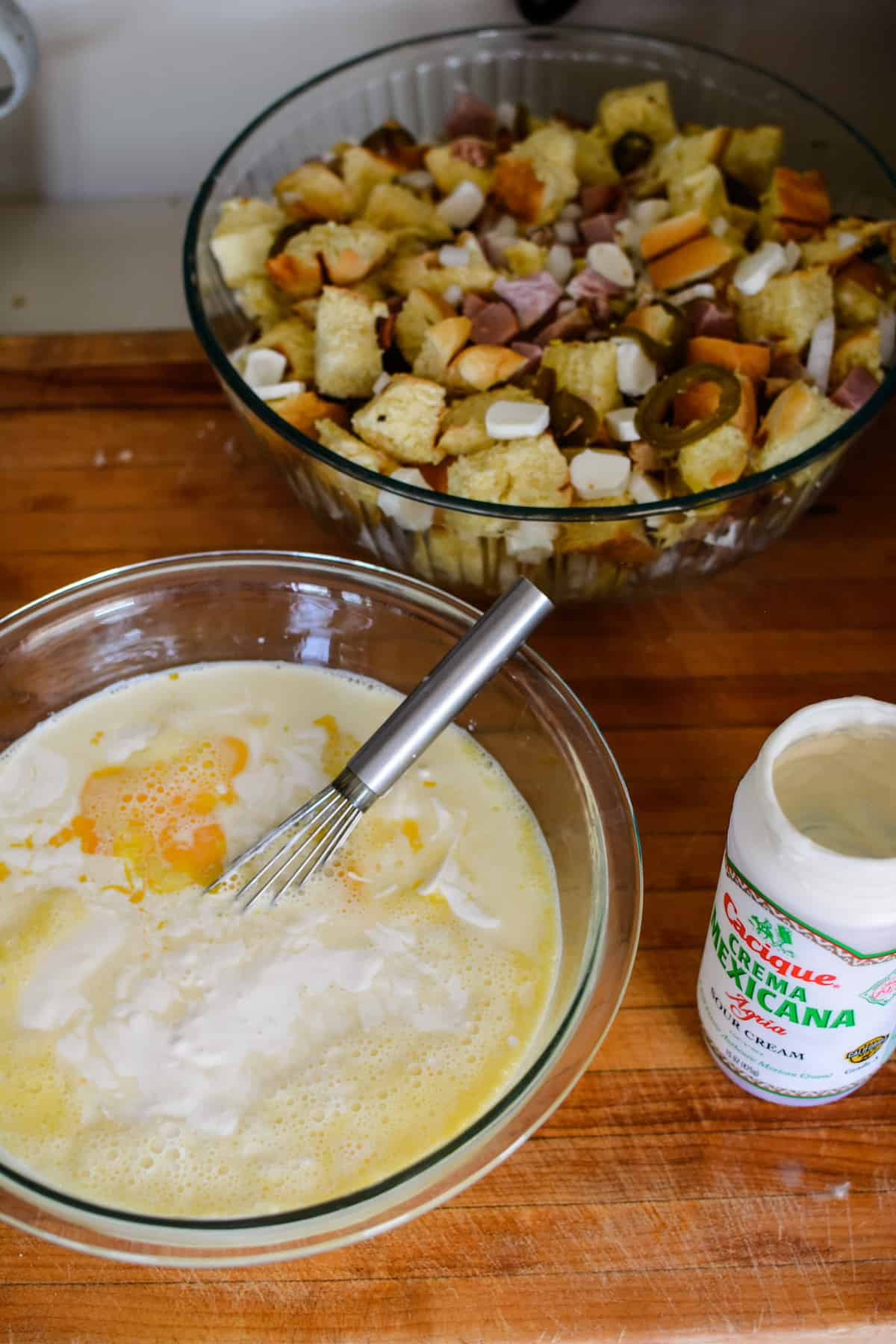 A large glass bowl with milk, eggs, and Mexican crema in it with a whisk in the bowl sitting on a wooden cutting board.