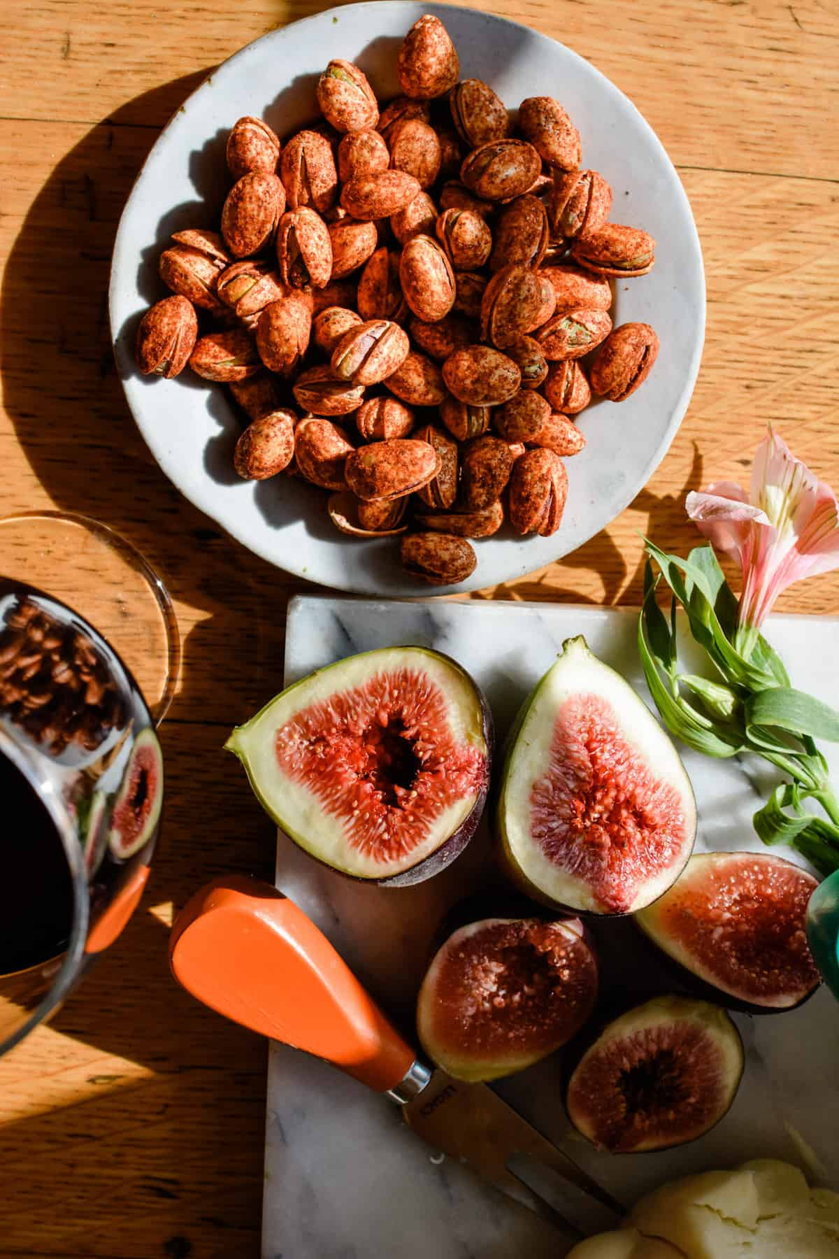 A small plate of chili-coated pistachios sitting on a wooden table with a glass of red wine near by and a few figs cut on a marble table.