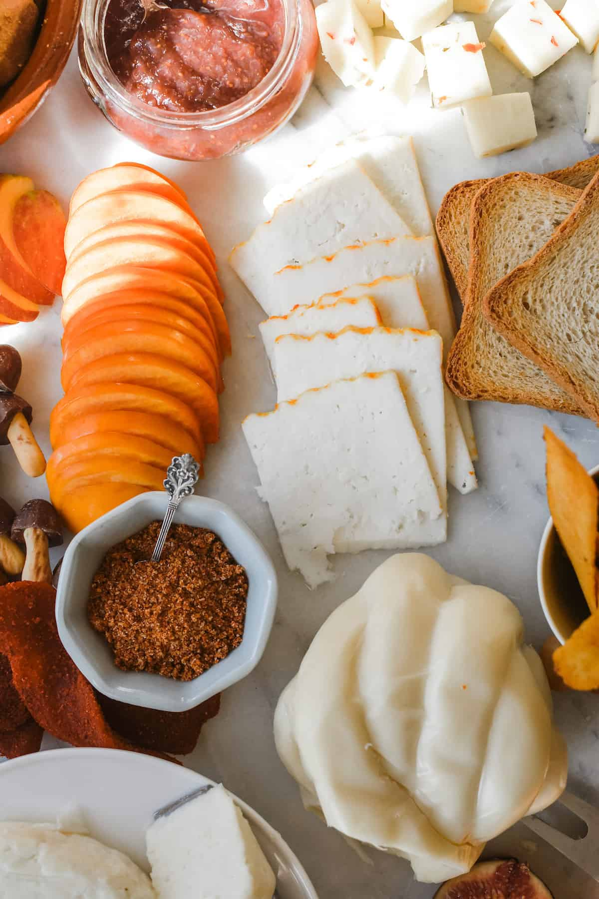 Thin slices of cheese laid out in a row next to slices of orange persimmon and pieces of toast with a ball of Queso Oaxaca on the edge.