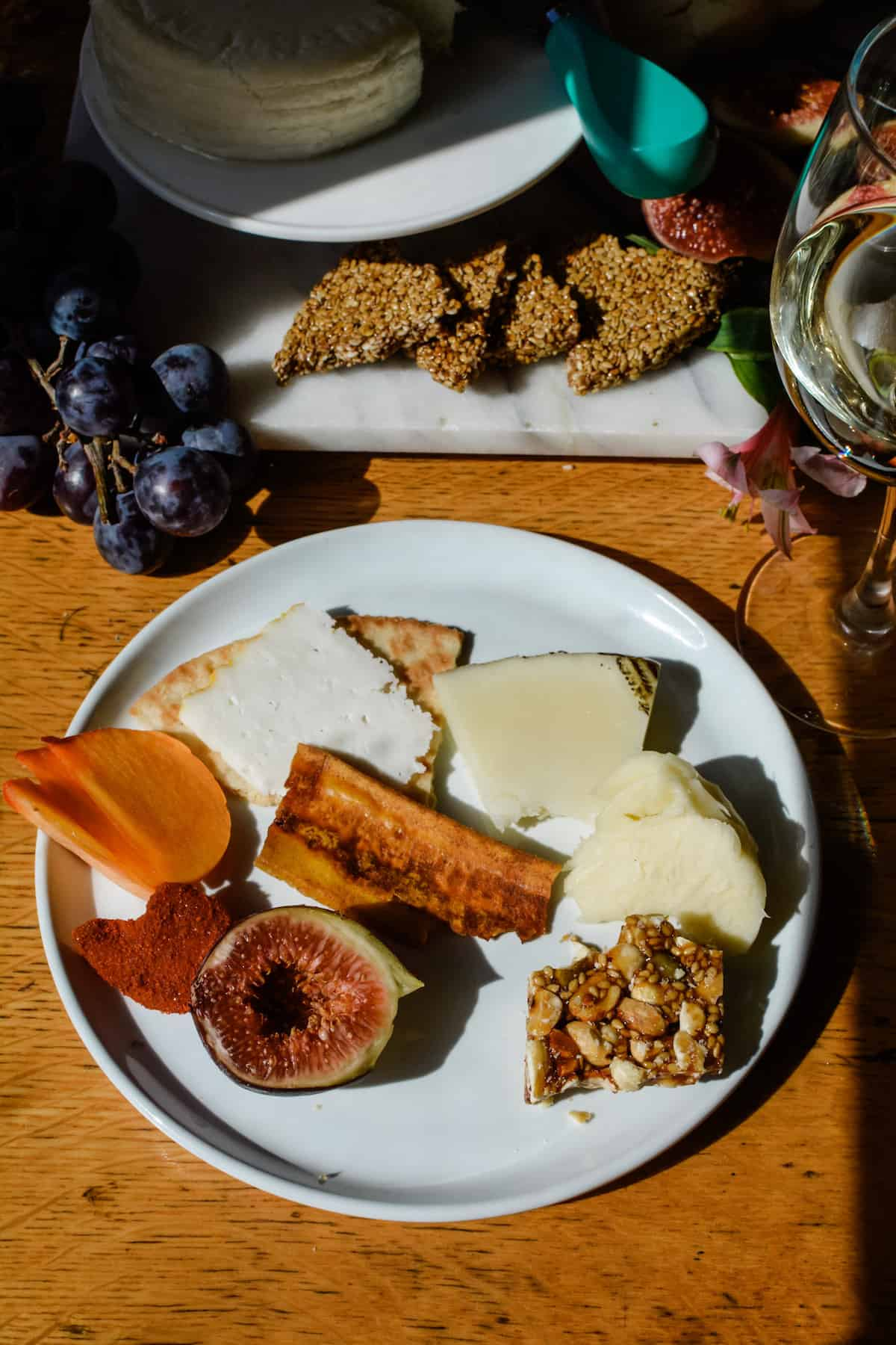 A white plate sitting on a wood table with pieces of cheese, a cracker, slices of persimmon, a half of a fig, and some nut brittle on it.