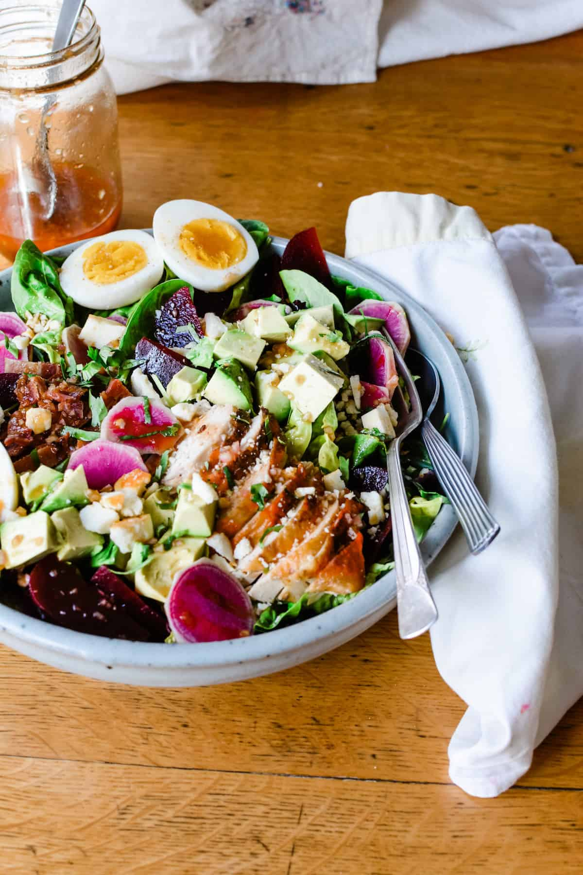 A Cobb Salad recipe made with chicken, feta, avocado, and lettuce in a big bowl on a wooden table.