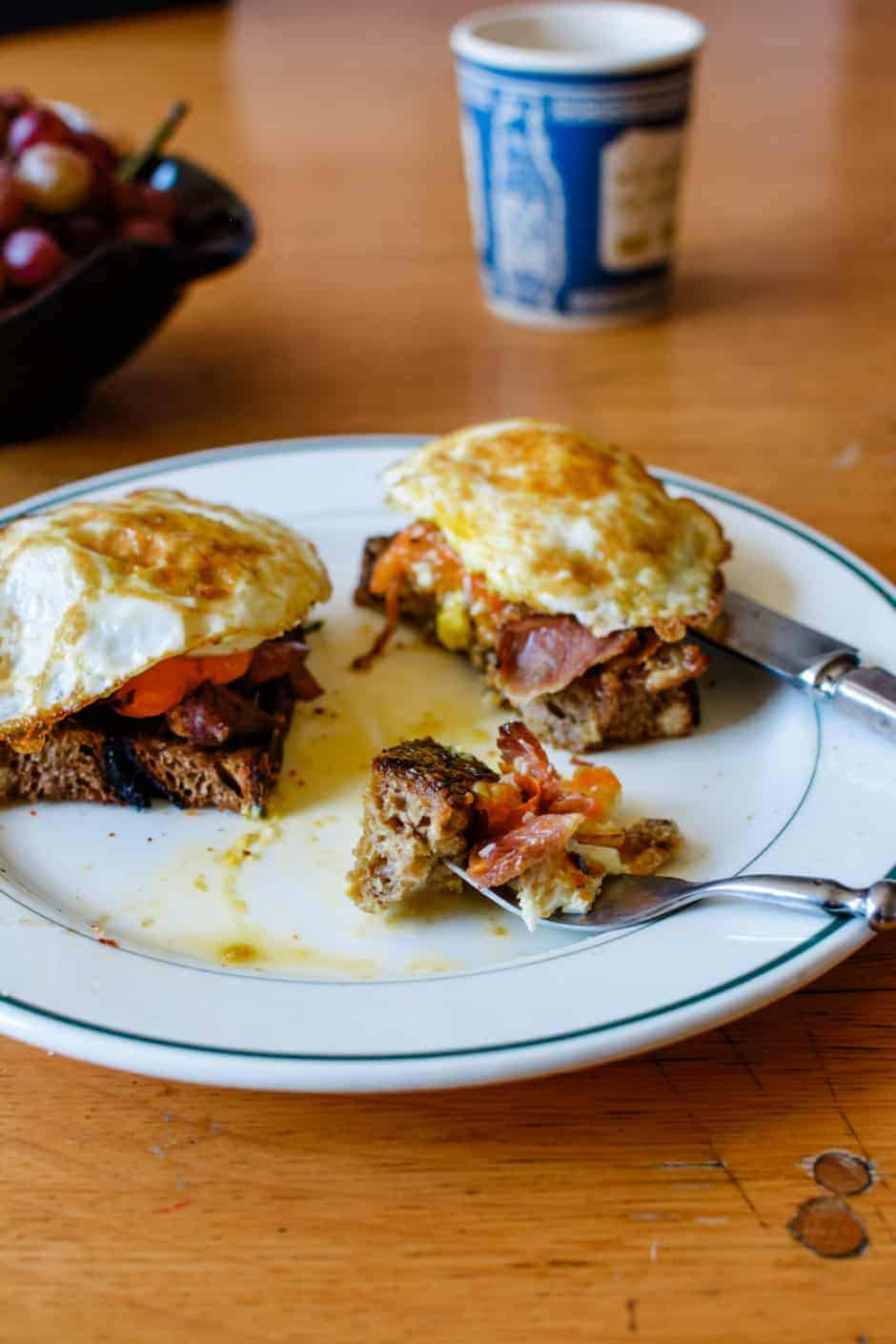 Such a delicious breakfast recipe: Slices of rustic bread rubbed with garlic and topped with ham, roasted tomatoes and mushrooms, and a fried egg.
