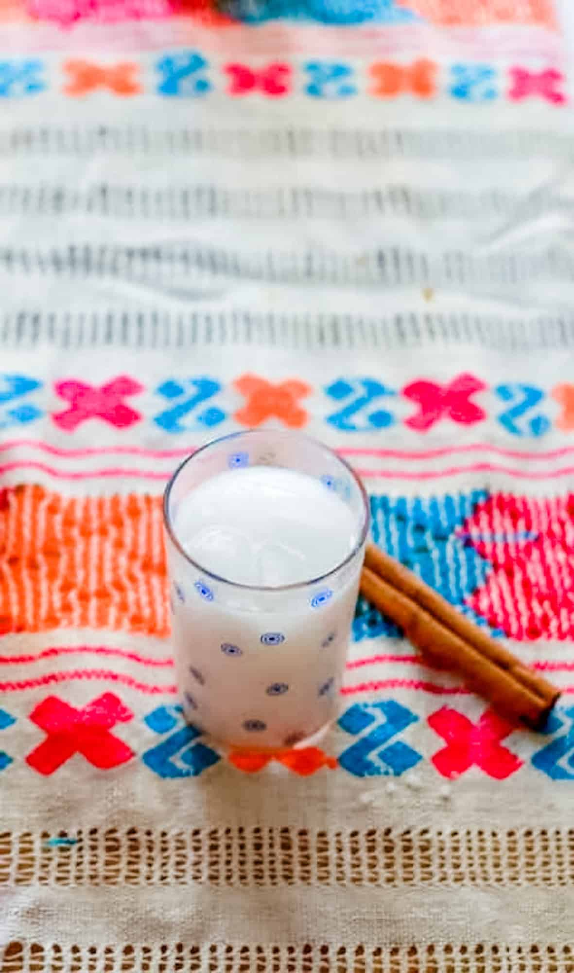 A cup of horchata sitting on a colorful tablecloth with a cinnamon stick next to it.