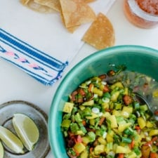 A green bowl with mango margarita salsa in it sitting on a white table with chips and a beer on the side.