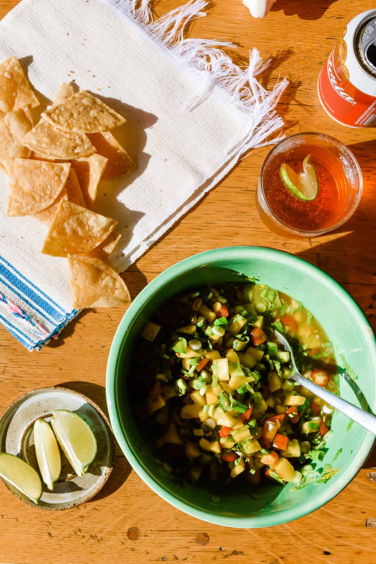 A green bowl with mango margarita salsa sitting on a wooden table with lime wedges, tortilla chips, and a beer on the side.