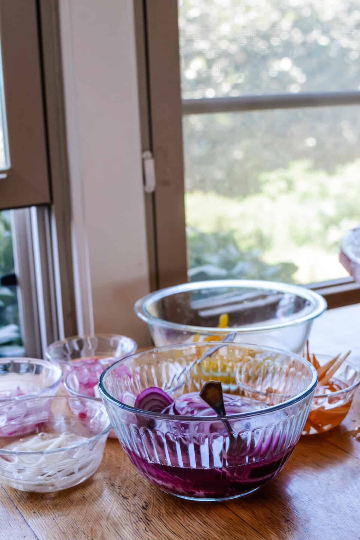 Several glass bowls sitting on a wooden table. The largest one has pickled red onions in it with a fork in the bowl.
