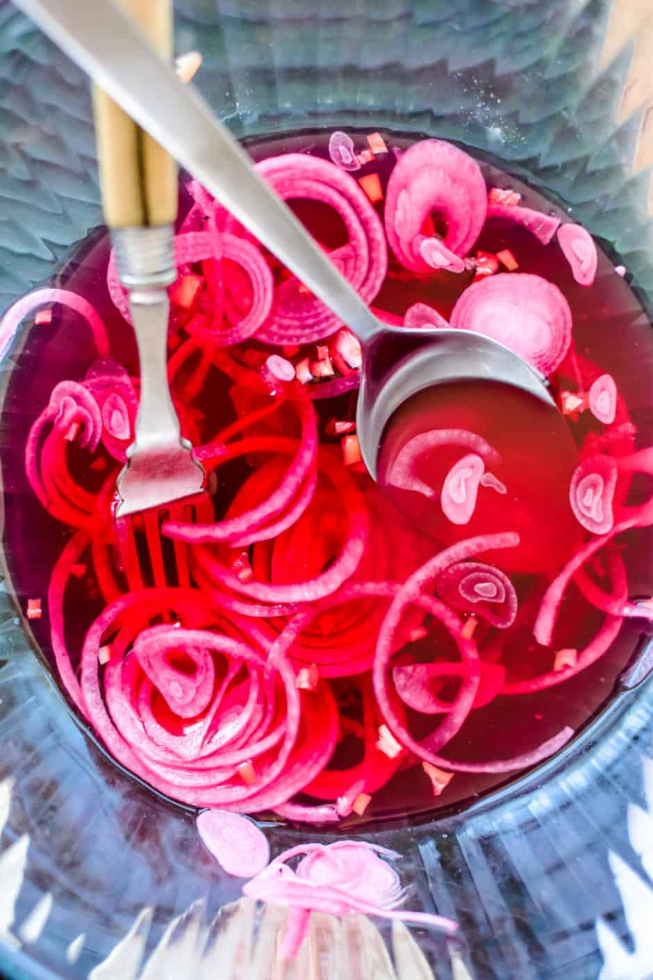 A glass bowl with sliced pickled red onions , a fork, and a spoon inside of it.
