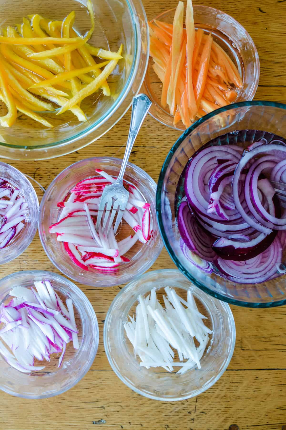 Overhead shot of several glass bowls with different sliced vegetables soaking in pickling liquid in each one.