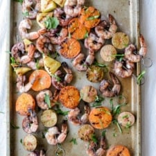 Overhead image of grilled shrimp skewers sitting on a baking sheet.