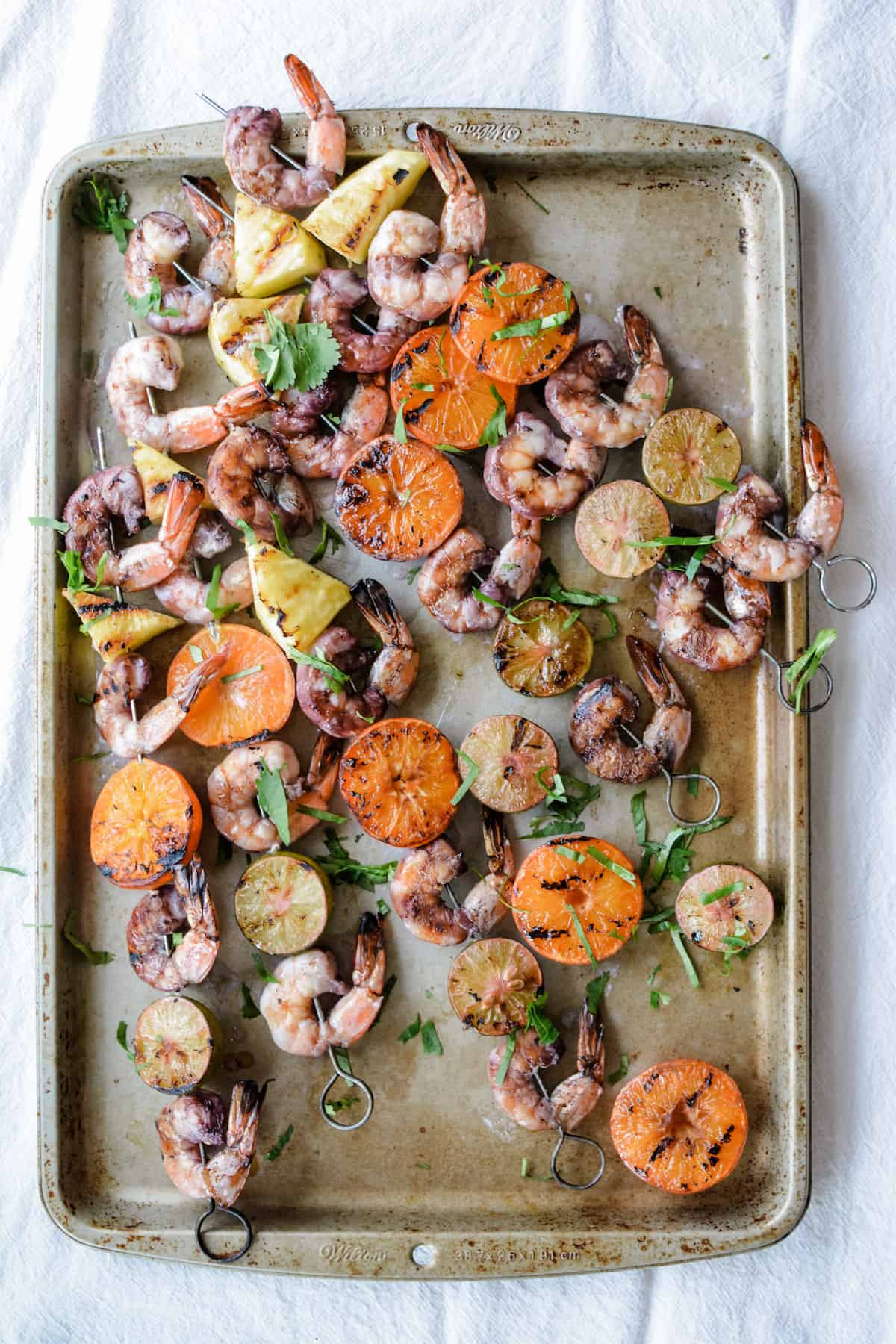 An overhead image of grilled shrimp skewers on metal skewers with shrimp, tangerine halves, pineapple, and key lime halves.