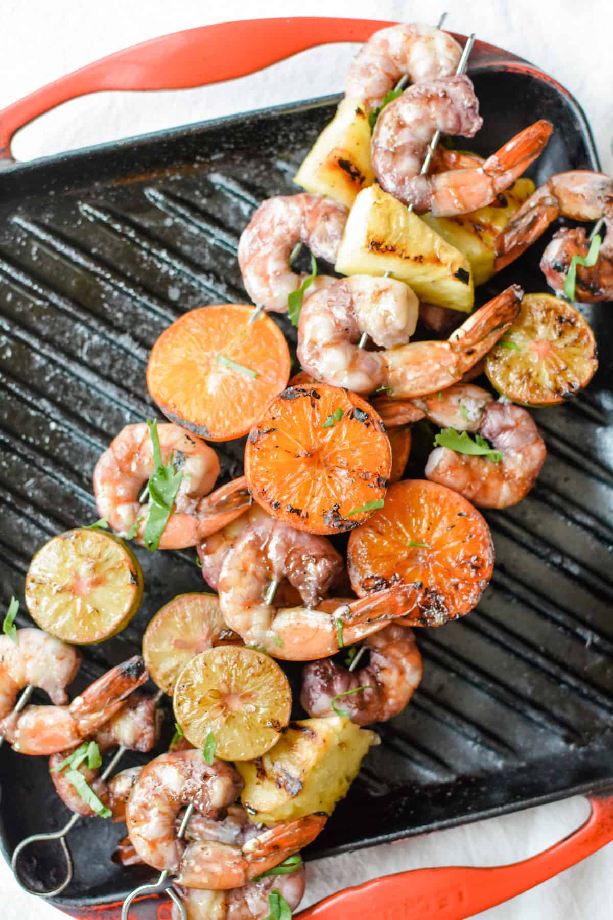 An overhead image of grilled shrimp skewers sitting on a grill pan with red edges.