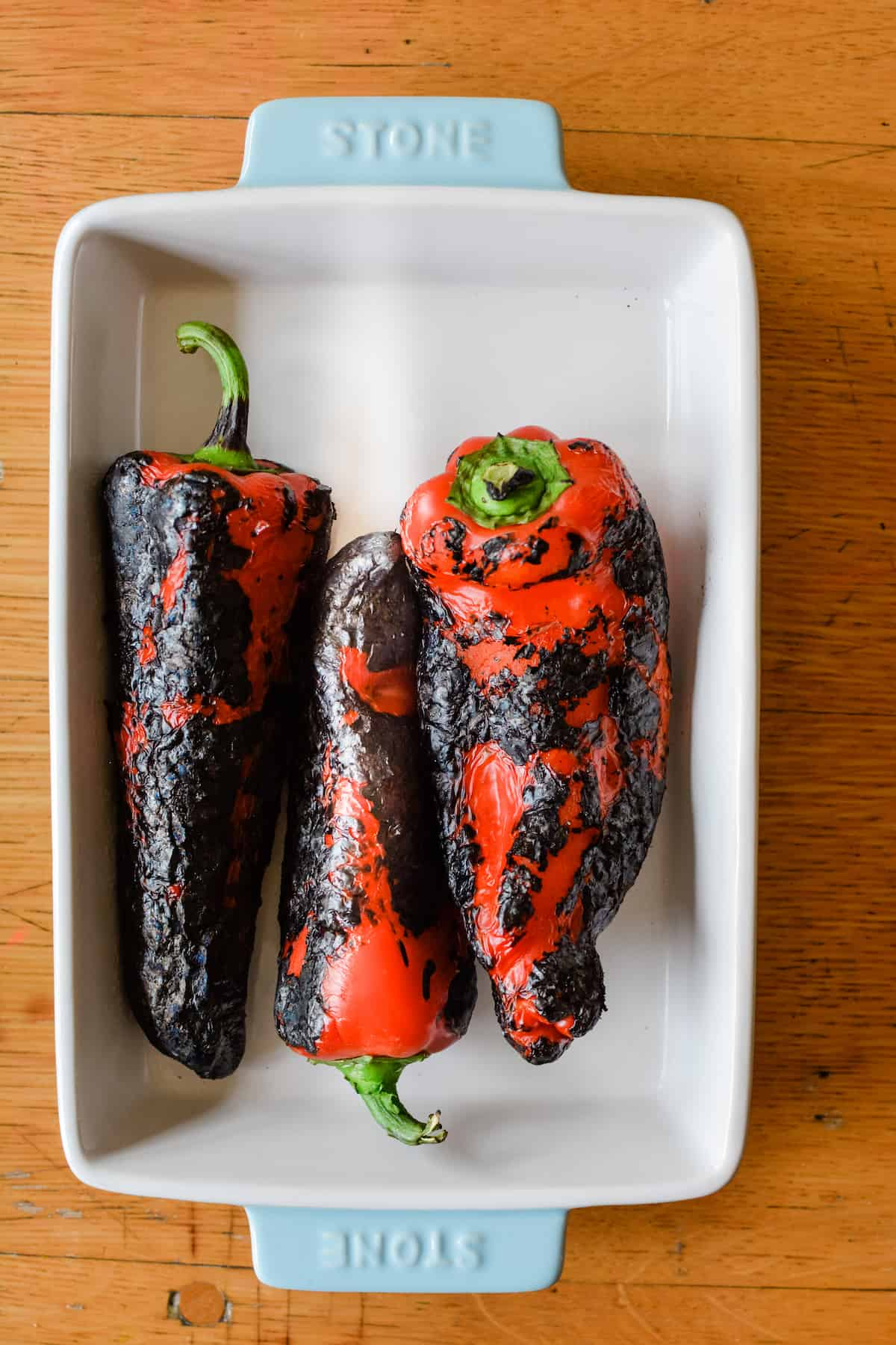 Overhead image of charred, roasted red bell pepper with blackened skin laying in a white ceramic baking dish with blue edges on a wood table.