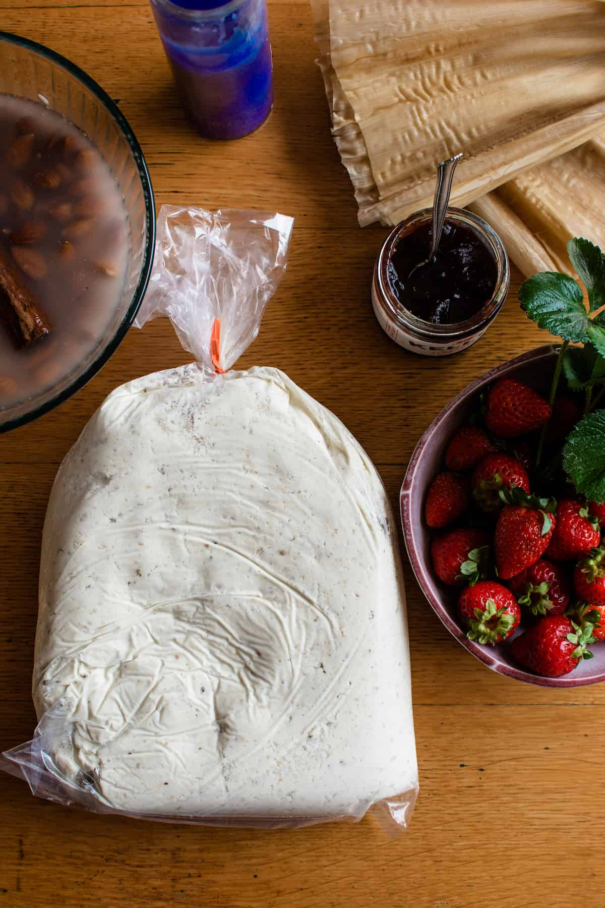 Ingredients for making strawberry tamales including fresh masa, strawberries, strawberry jam, corn husks on a wood table.