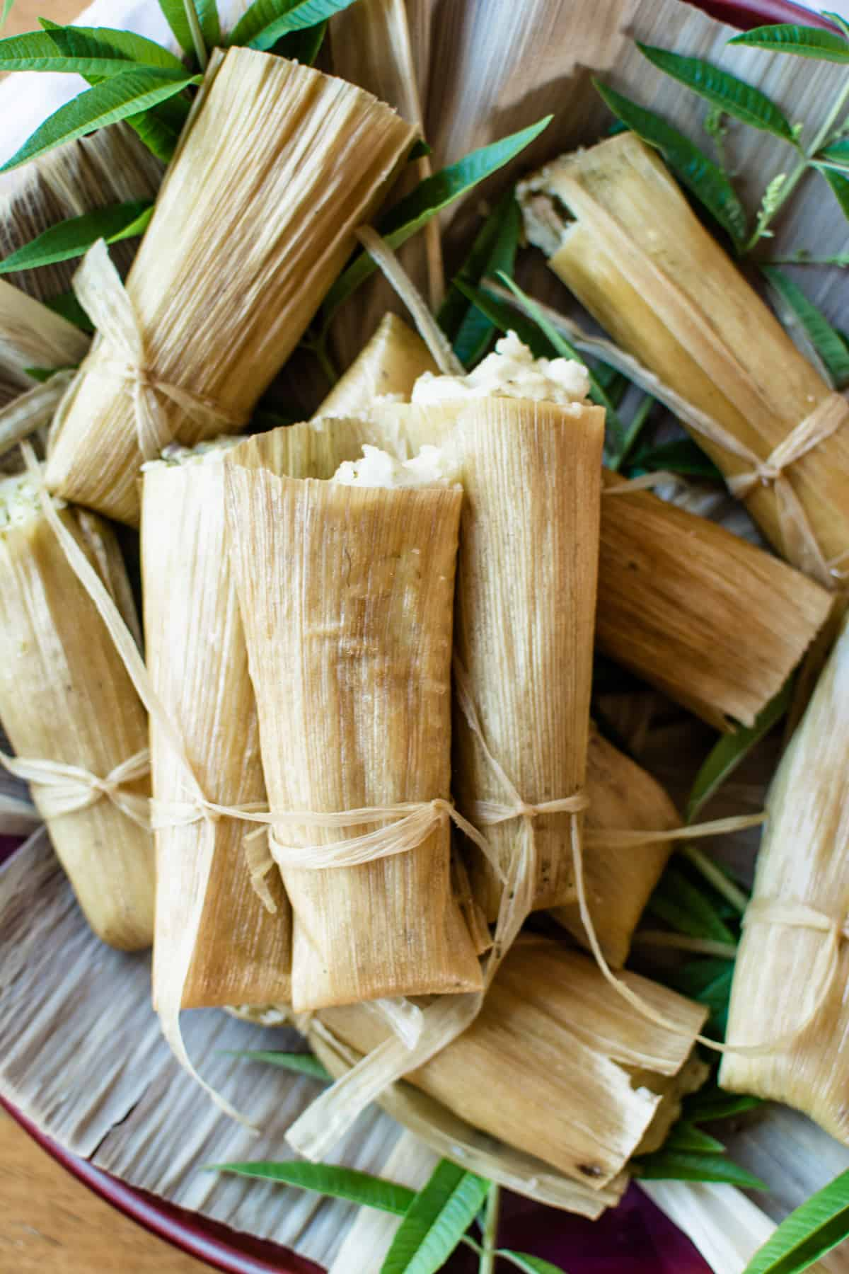 Several pork tamales wrapped in corn husks and tied with corn husk strings sitting on a platter covered in corn husks and green leaves.