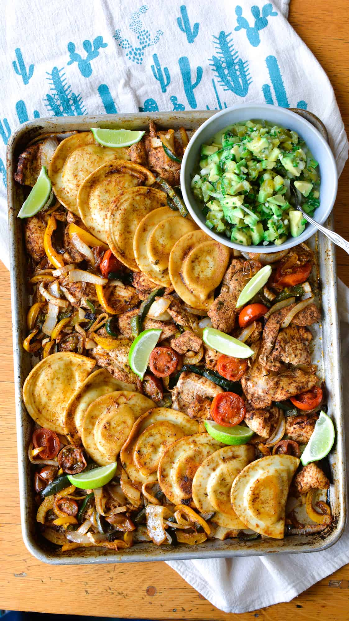 An overhead image of a sheet pan of chicken fajitas with Pierogies and a bowl of avocado salsa sitting on the sheet pan.