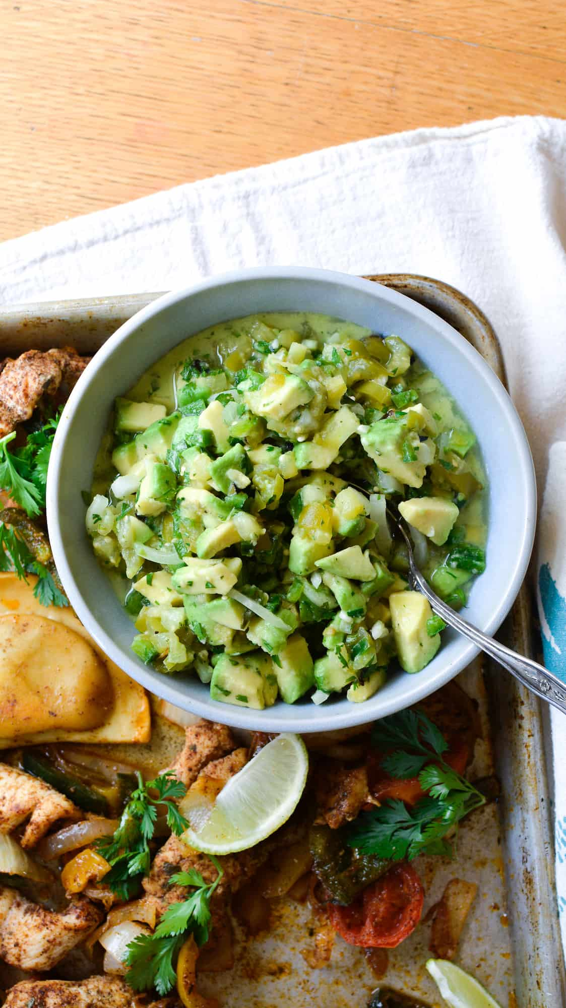 An overhead image of a bowl of avocado salsa with a spoon in the bowl sitting on a baking sheet on a wood table.