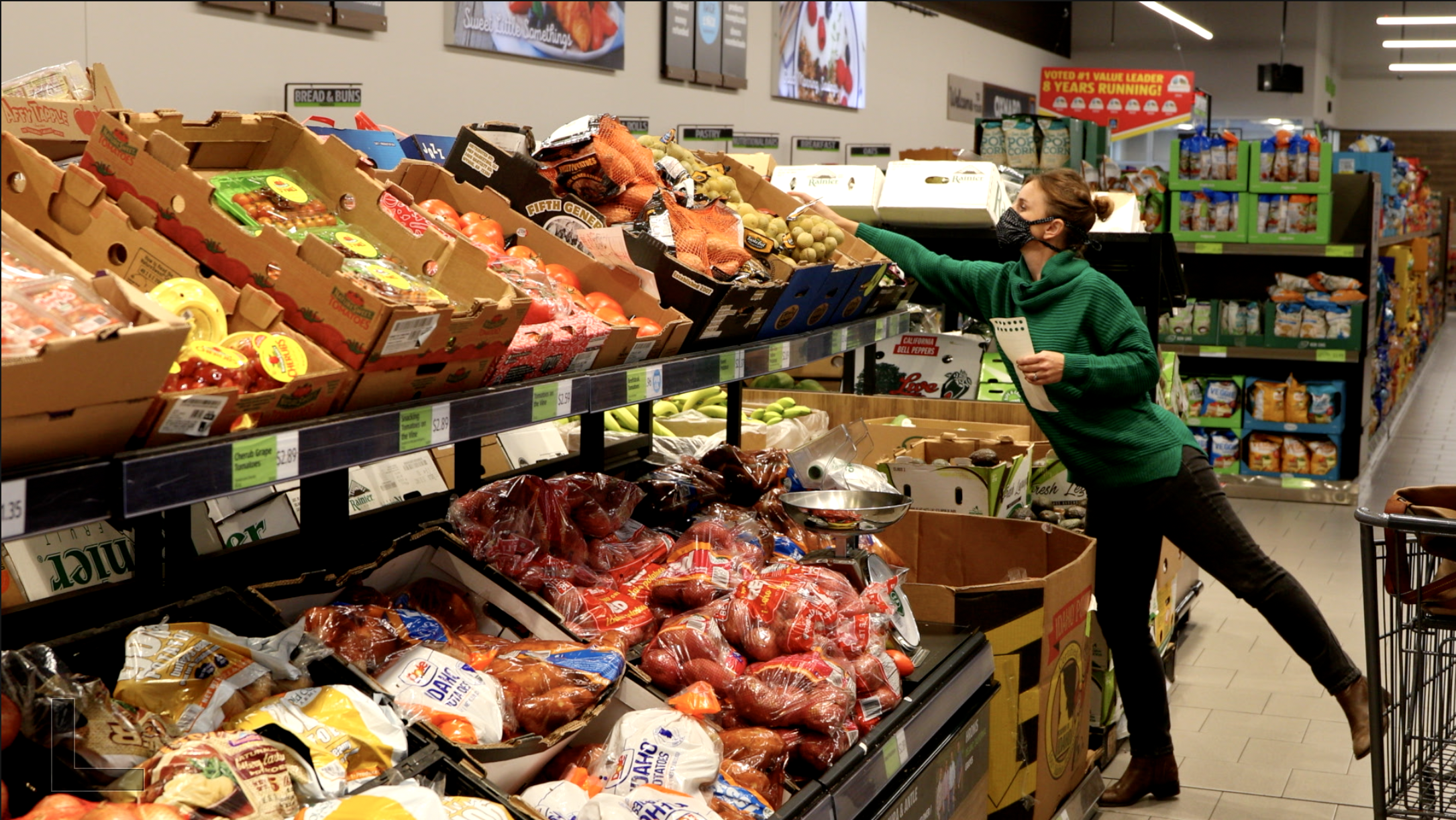 A woman shopping at a grocery store in the produce section, reaching to get something from a high shelf with boxes of potatoes in front of her.