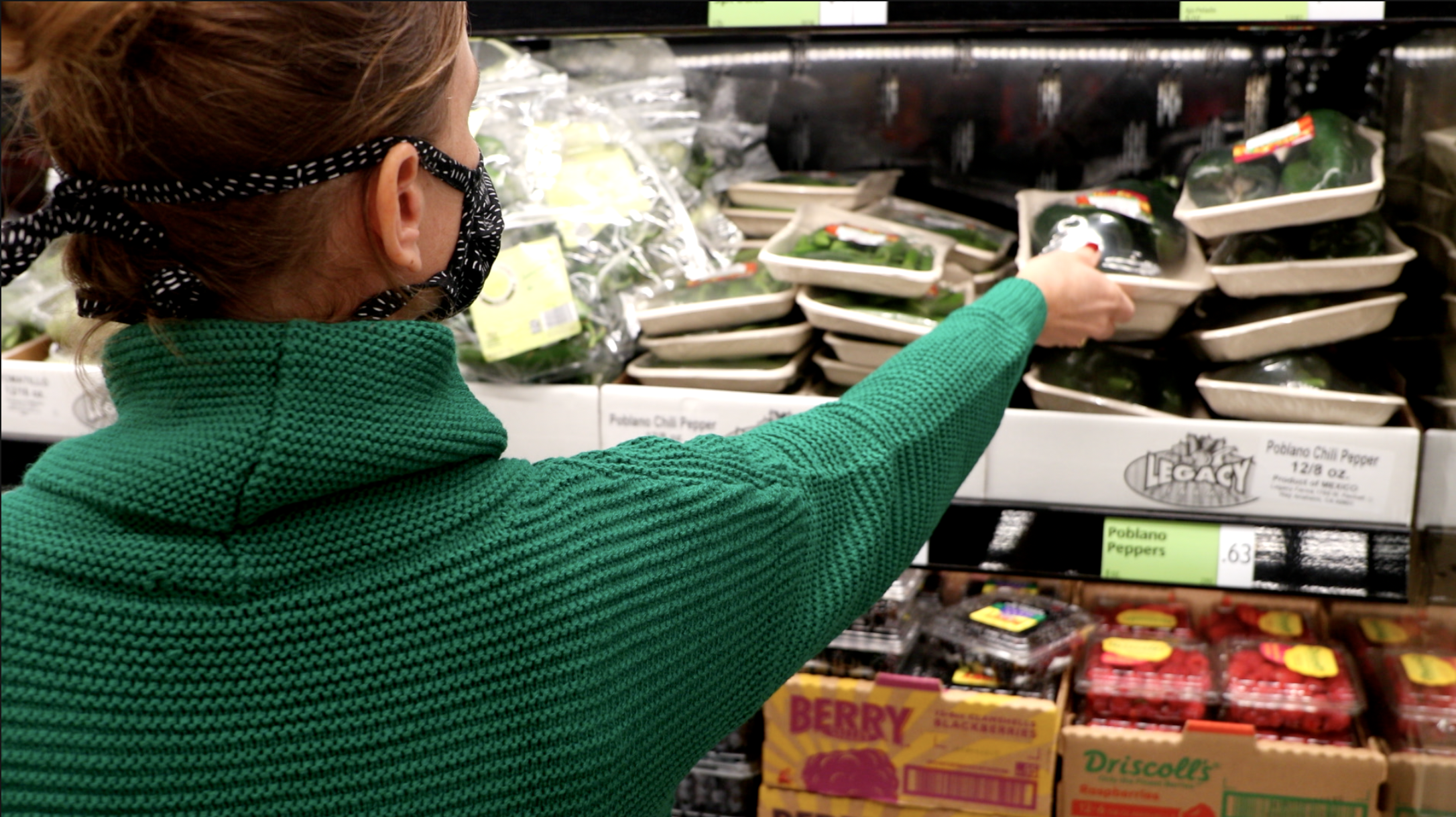 A woman in a green sweater reaching for a package of poblano peppers at a grocery store. With raspberries on a lower shelf.