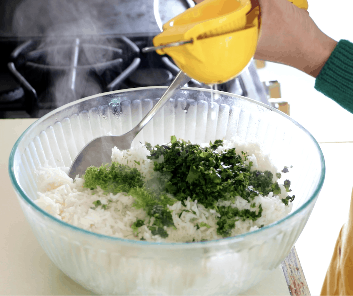A clear bowl sitting on a counter with steaming white rice and cilantro in it. A person is squeezing a yellow lemon squeezer over the top.