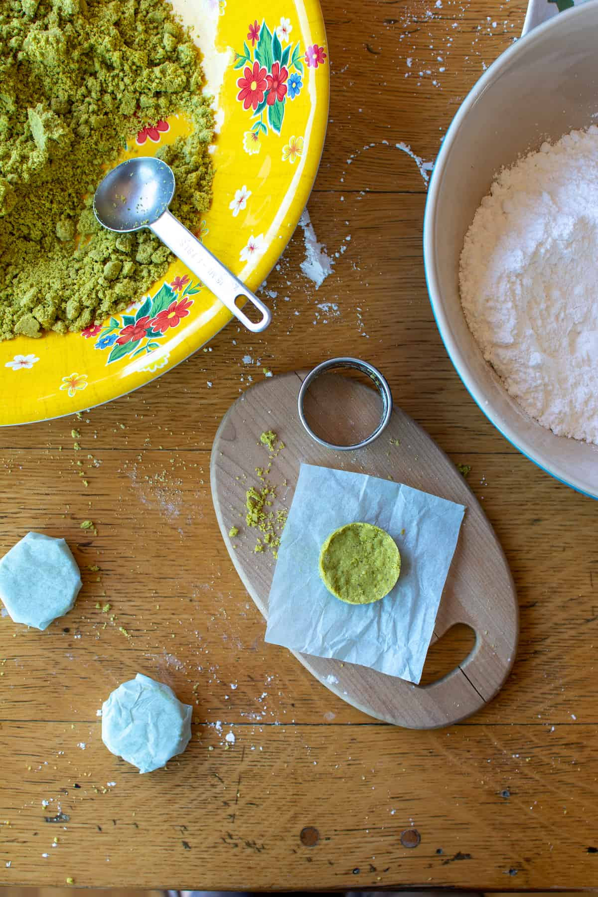 Overhead image of pistachio mazapan candy being wrapped in light blue tissue paper sitting on a small wood cutting board.
