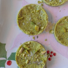 Overhead image of pistachio mazapan a green round candy with crushed pistachios and flaky salt on top.