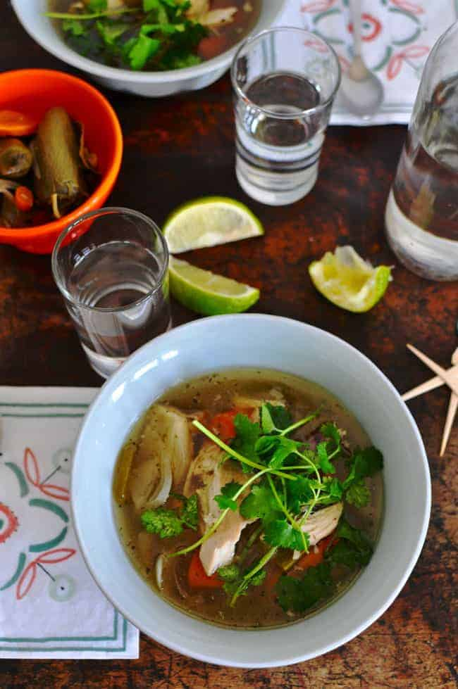 Overhead image of a bowl of Caldo de Pollo or Mexican Chicken Soup topped with fresh cilantro leaves sitting on a wood table.