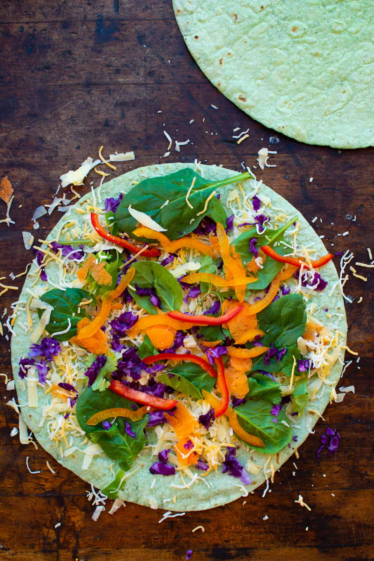 Overhead image of a veggie quesadilla with shredded cheese on a spinach flour tortilla sitting on a wood table.