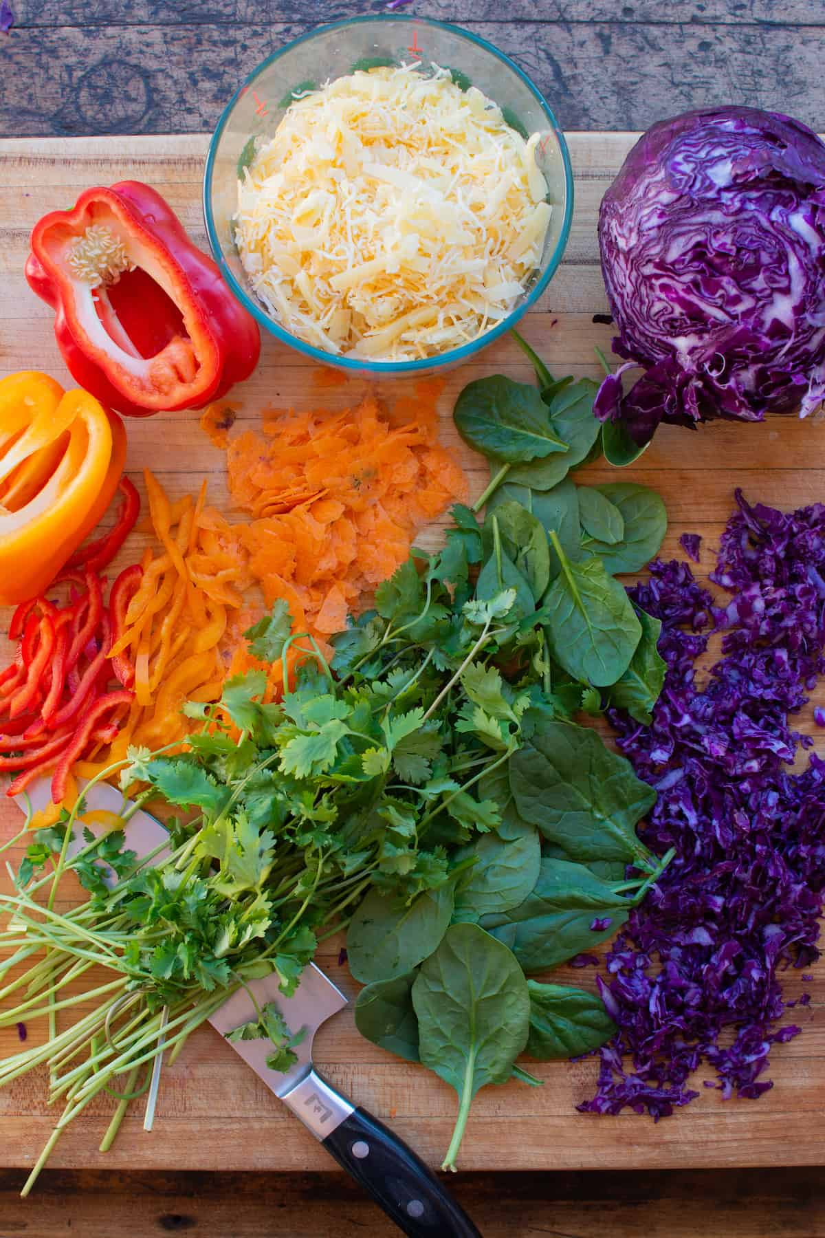 Overhead image of ingredients needed to make veggie quesadillas. Chopped red bell pepper, orange bell peppers, carrots, cilantro, and spinach.