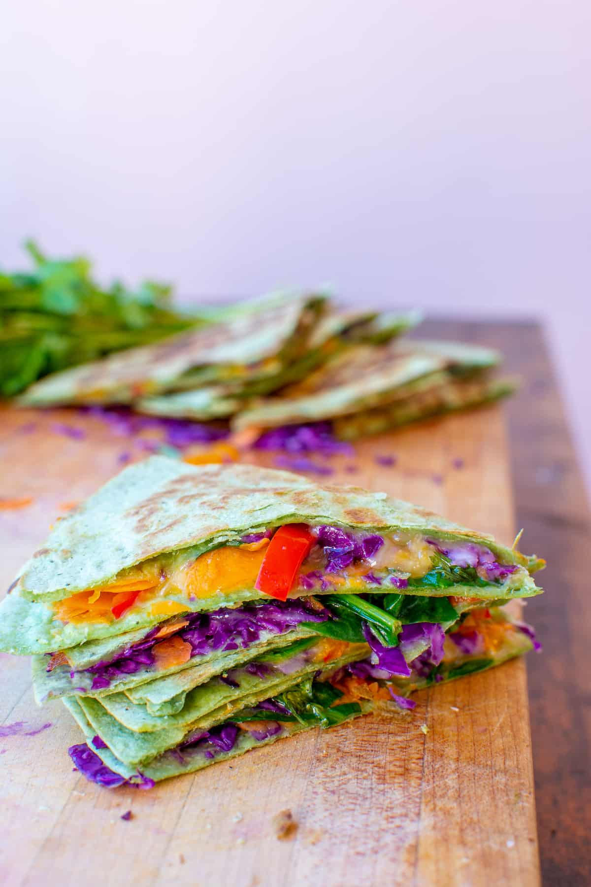 A stack of vegetable quesadilla slices sitting on a cutting board on top of a wood table with bell peppers, red cabbage, and cheese.