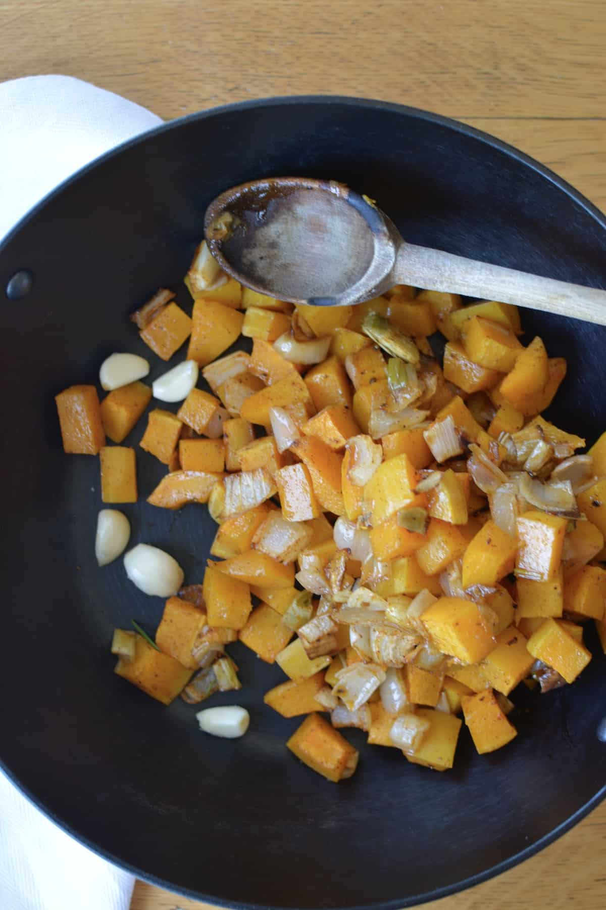 An overhead image of hunks of roasted squash, onions, and cloves of garlic in a black pot with a wooden spoon sitting on top.