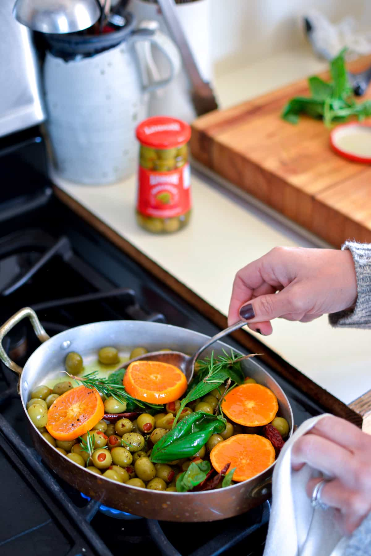 A person warming green, pimento-stuffed olives on the stove with tangerine slices, and fresh herbs in a copper pan.