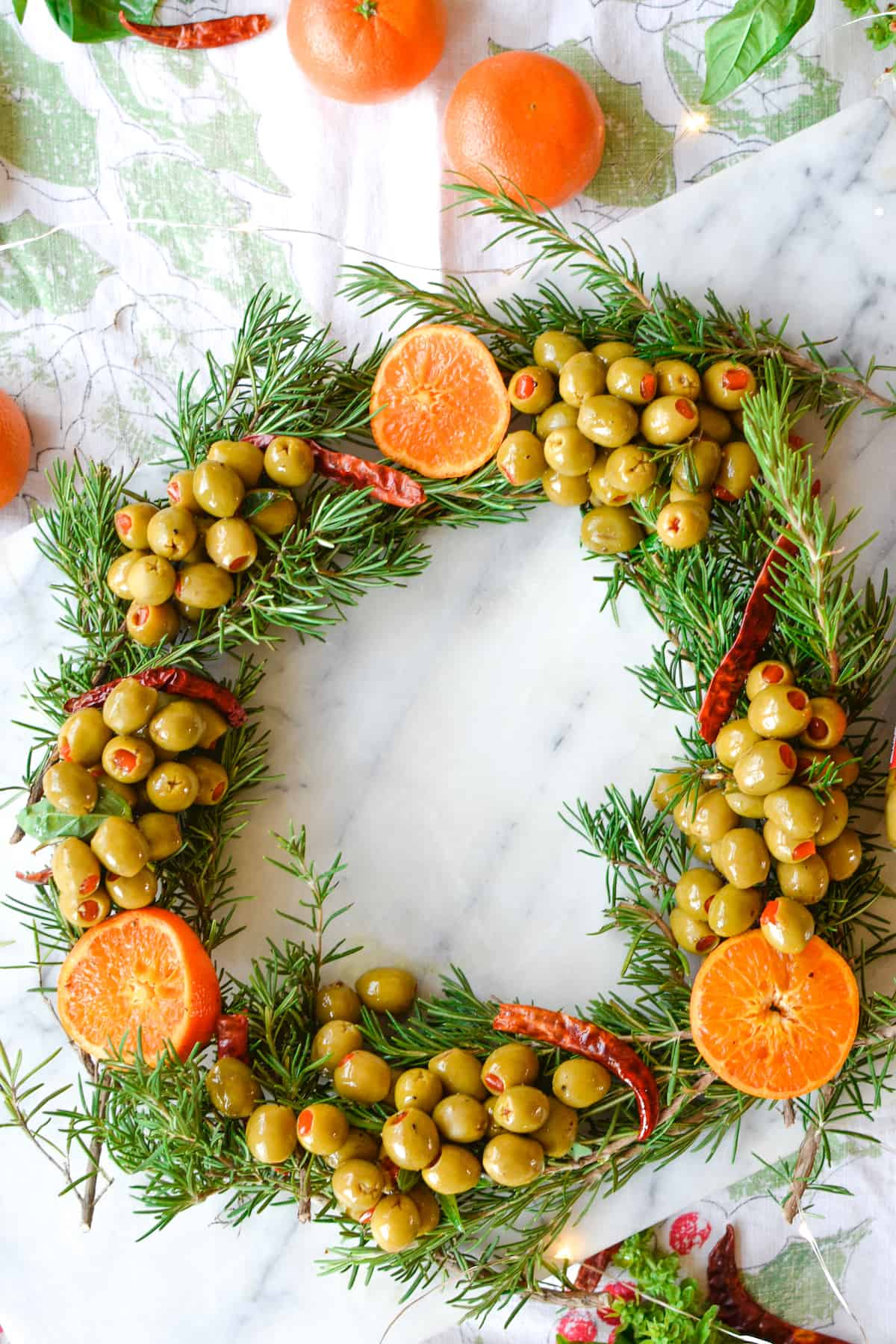 A super easy holiday appetizer recipe made with briny olives warmed with fresh tangerine slices, arbol chiles, and black pepper and shaped into a wreath with fresh rosemary. Very impressive indeed! #holidayappetizer #wreathappetizer #olivewreath #marinatedolives