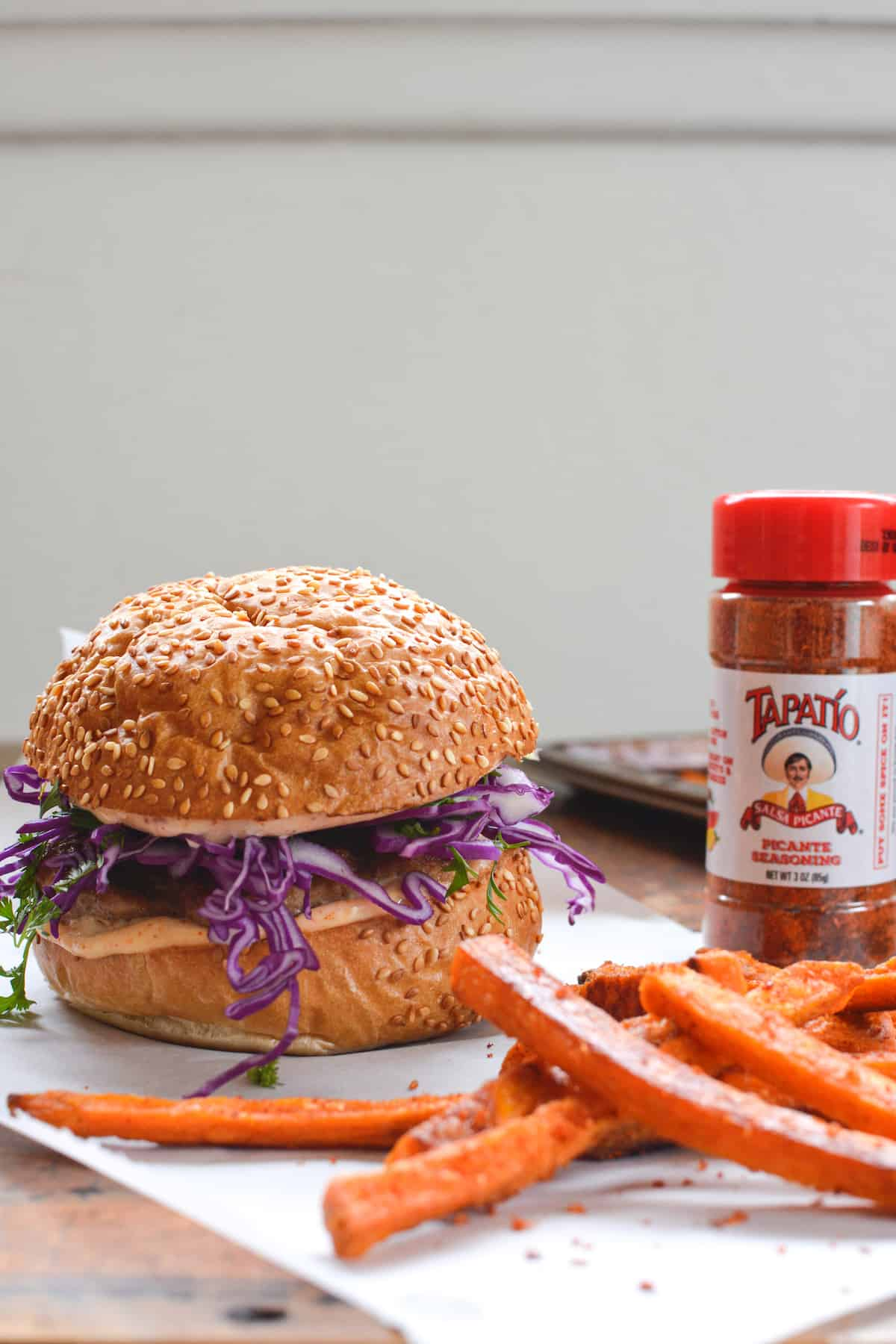 A turkey burger and sweet potato fries sitting on a piece of parchment paper on a wood table with a bottle of Tapatio spice mix next to it.