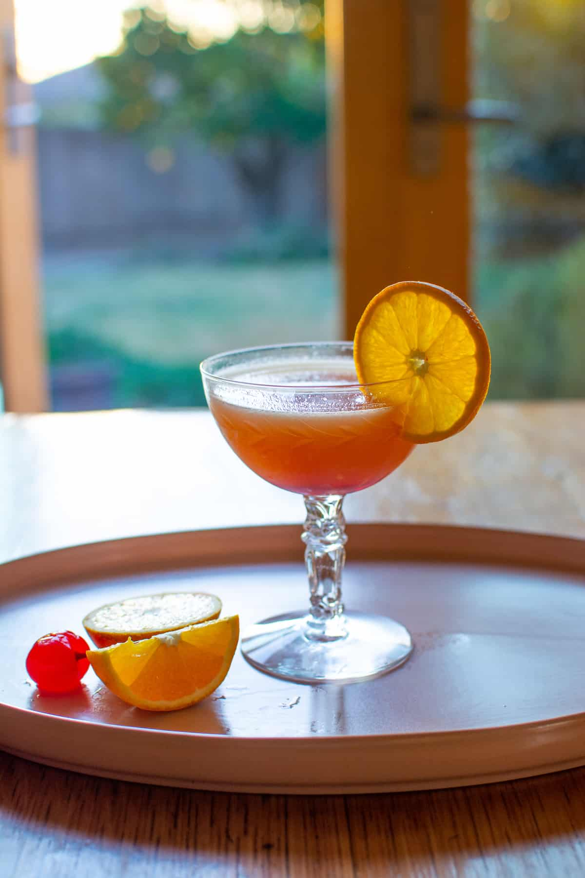 A tequila sunrise cocktail sitting on a wood table in front of an open door.