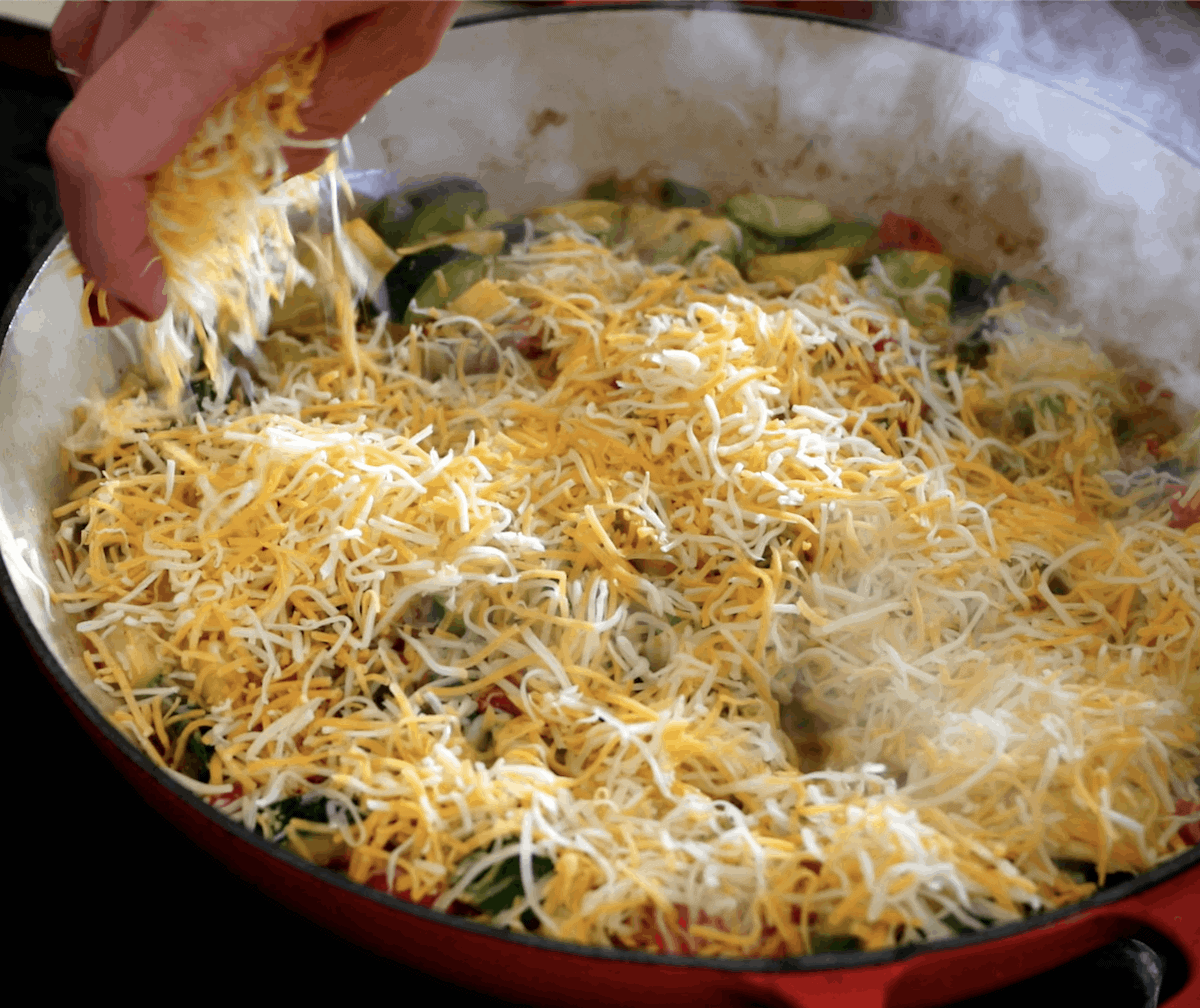 A pan of calabacitas on the stove with a hand sprinkling cheese all over the top.