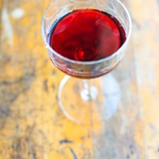 A glass of prune cordial sitting on a wood table.