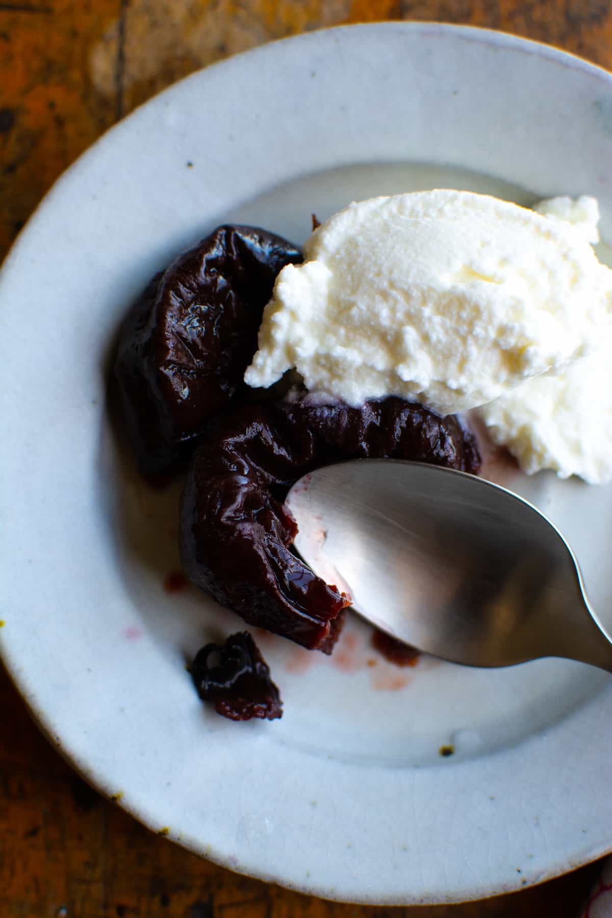 A white plate on a wood table with tequila-soaked prunes and a scoop of ricotta cheese.