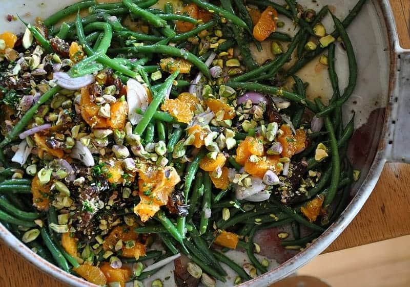 A ceramic dish filled with green beans tossed with tangerines, shallots, pistachios, dates.