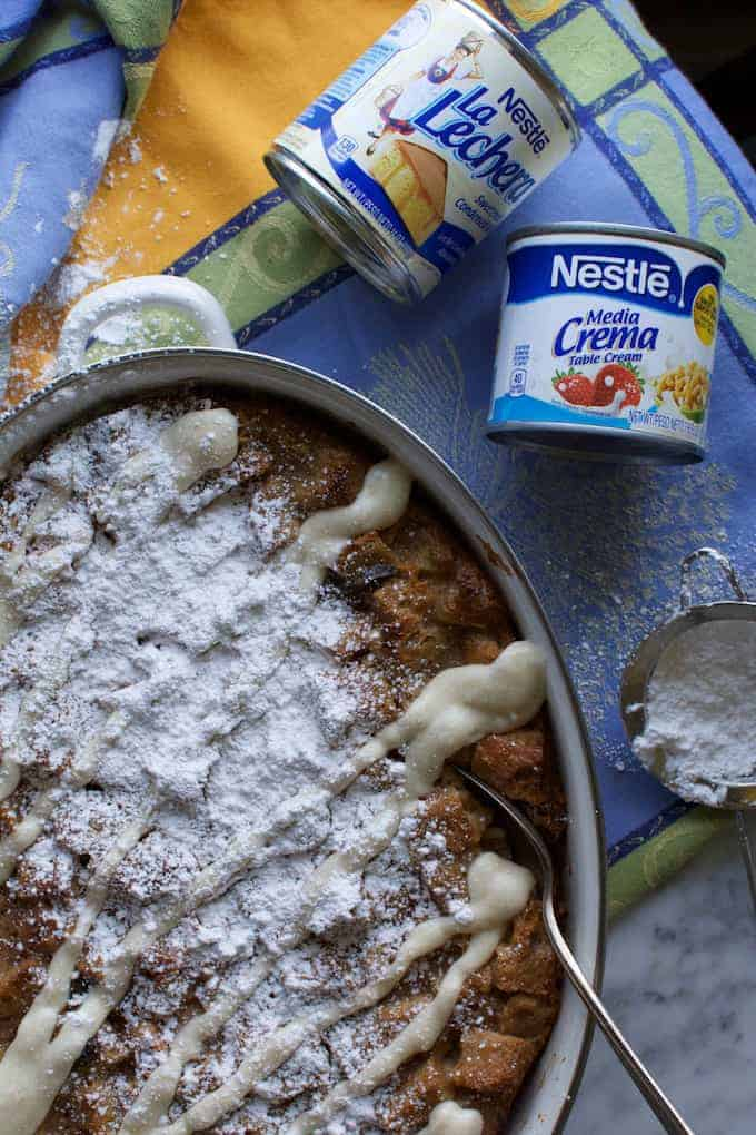 A dish of capirotada on a blue and yellow tablecloth with cans of sweetened condensed milk and media cream near by.