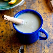 A mug of atole with a cinnamon stick sticking in the mug sitting on a wood table with a small plate of oranges behind it.