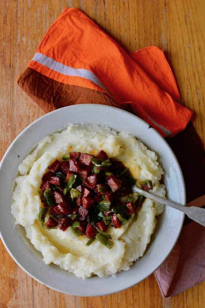 A bowl of mashed potatoes with chorizo and poblano pepper on top and a spoon sticking into the bowl.