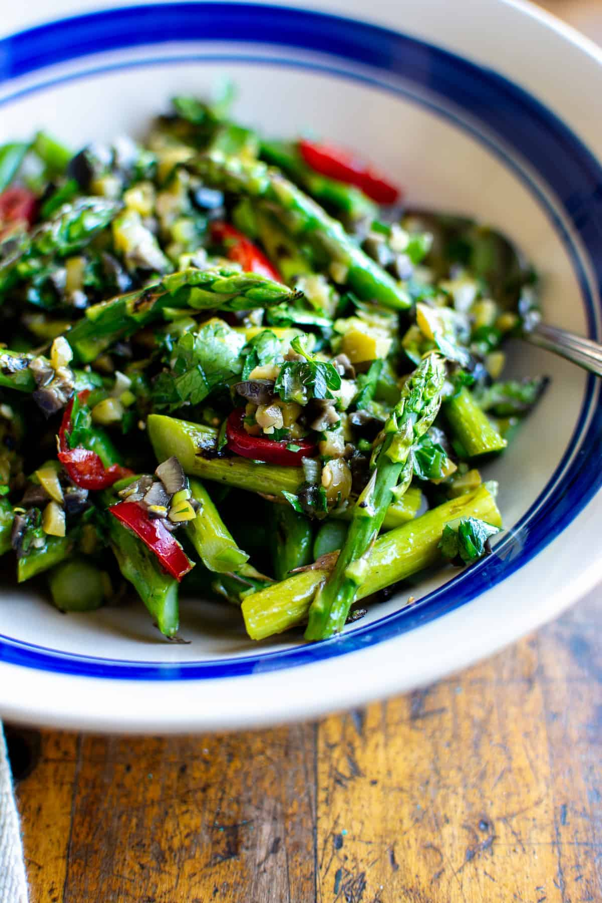 A close up of an asparagus salad with olive dressing in a white bowl with a blue line around the edge and a spoon sticking in one side.