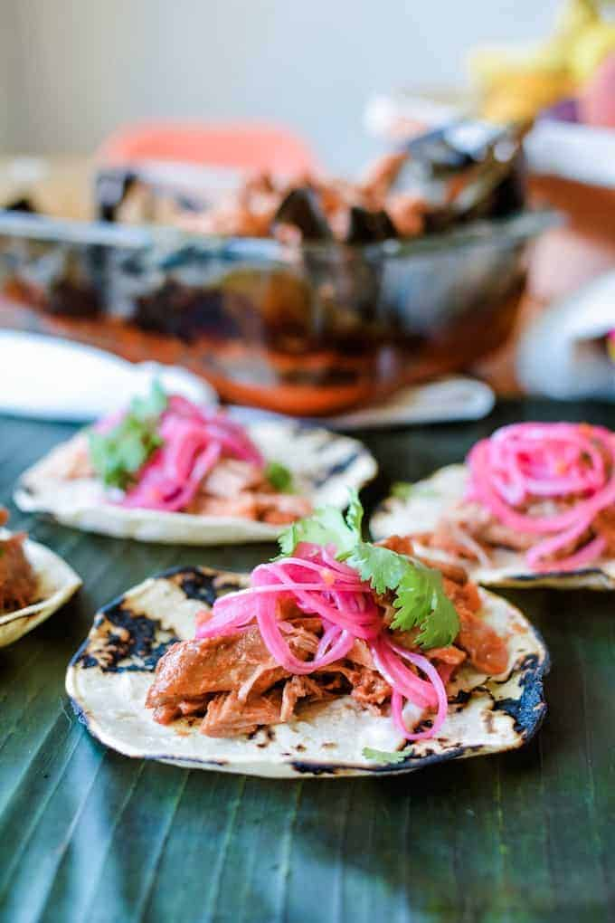 Cochinita Pibil tacos with pickled red onions on top sitting on a banana leaf with a dish of cochinita behind it.