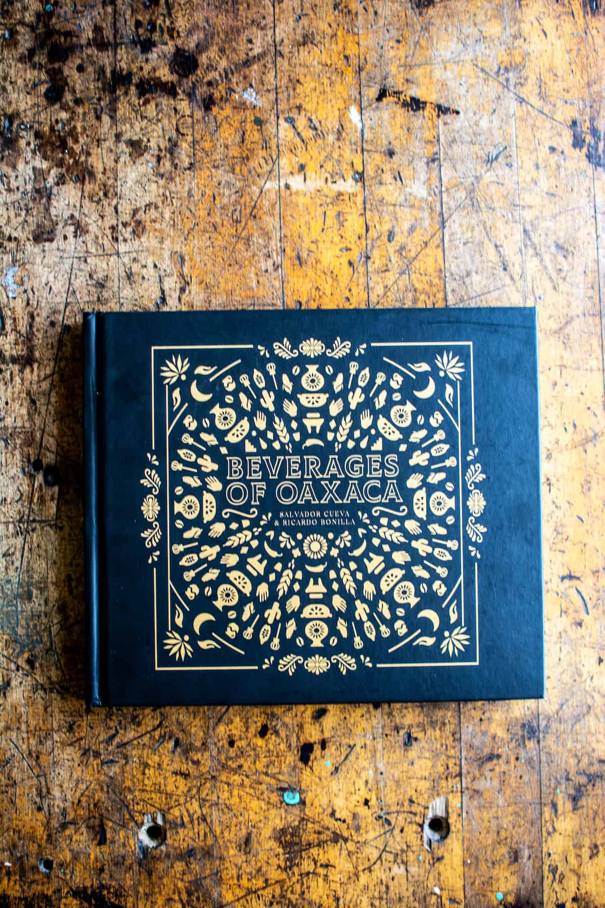 A black book with gold lettering and design sitting on a wood table. The title of the book is Beverages of Oaxaca by Salvador Cueva and Ricardo Bonilla.
