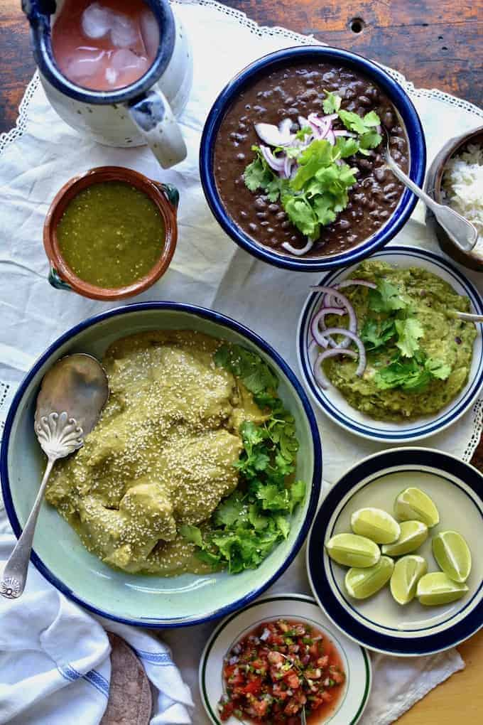 A dish of green mole chicken sitting on a table surrounded by a dish of black beans, guacamole, salsa verde, lime wedges.