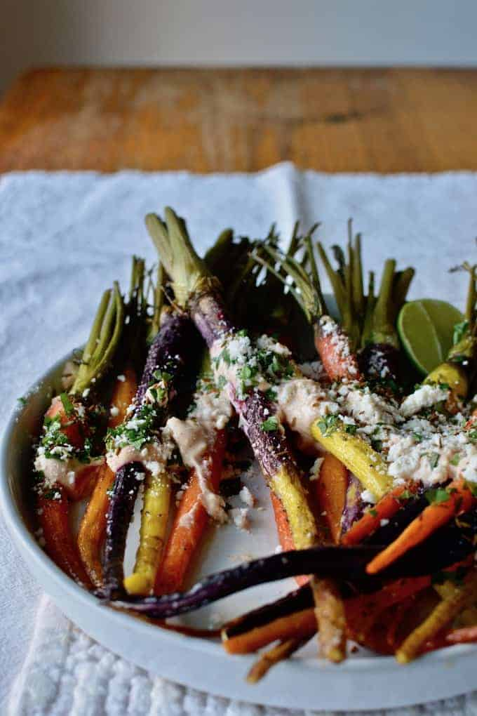 A white plate with rainbow carrots that have been roasted sitting on top with cream and cheese and a lime sitting near by.